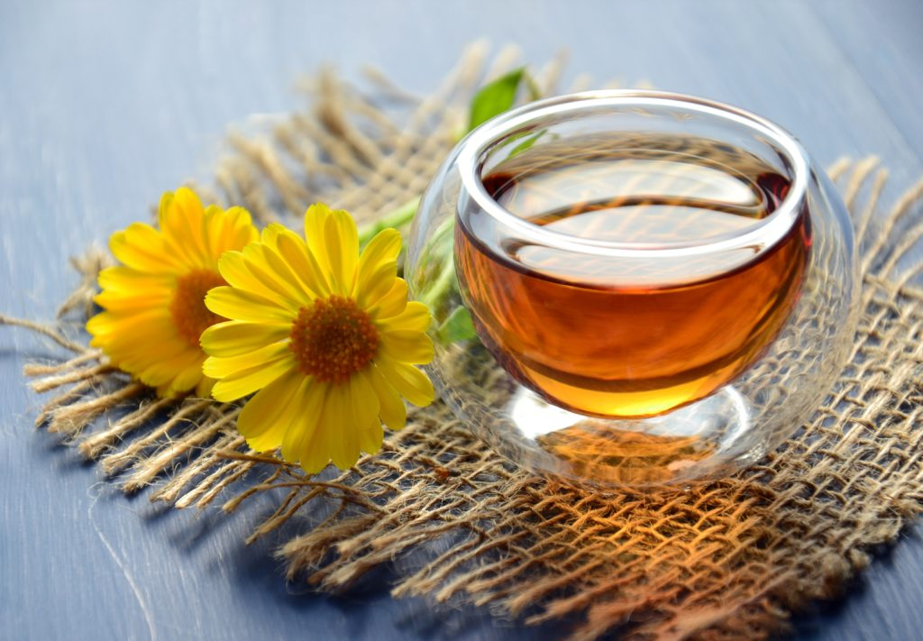 Glass of herbal tea with yellow flowers laying next to it