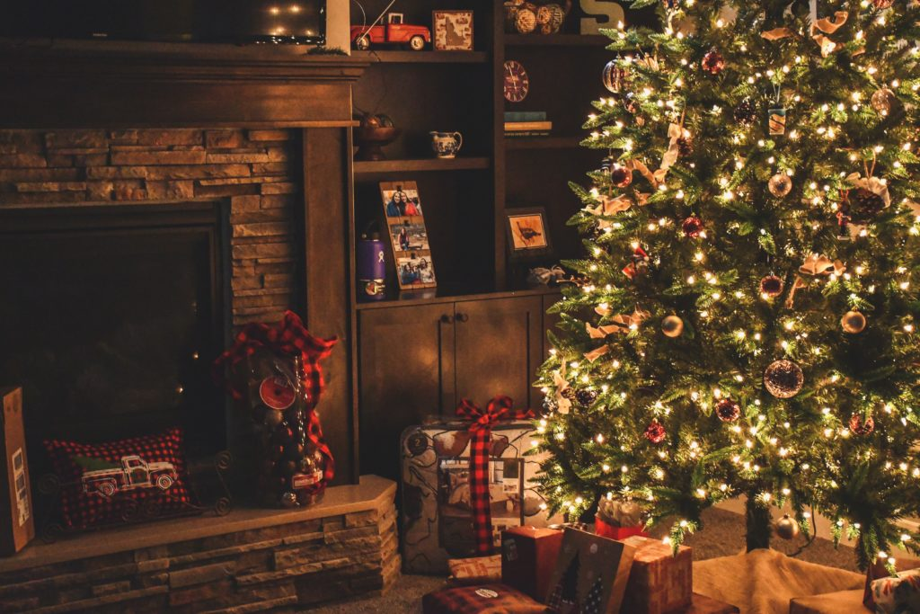 Christmas tree next to a fire place