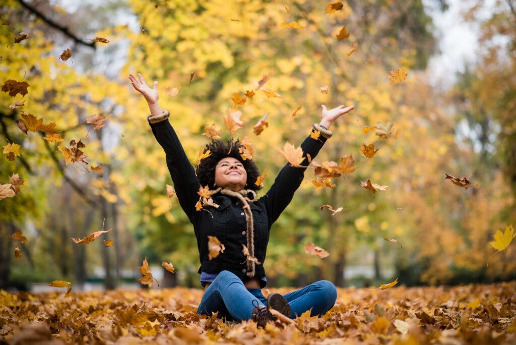 Mujer feliz en el parque otoño cayendo