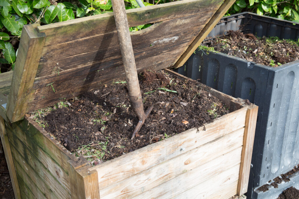 A wooden compost bin with the lid open