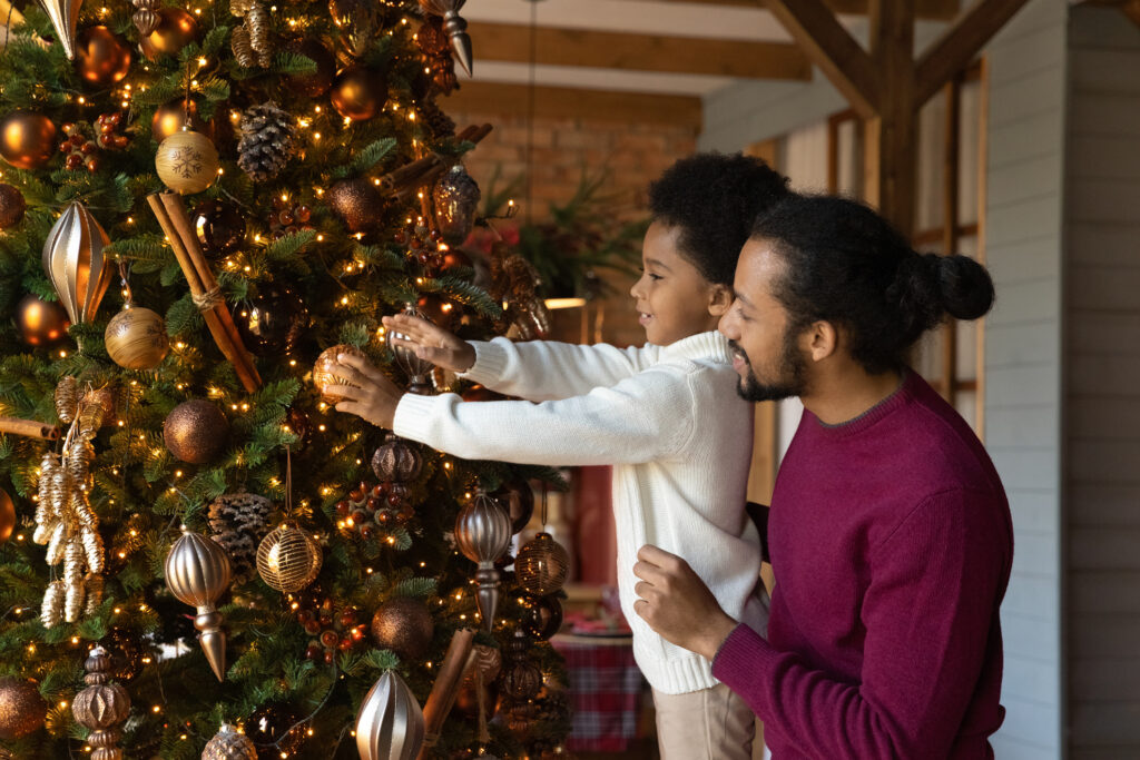Loving African American father with little son decorating Christmas tree