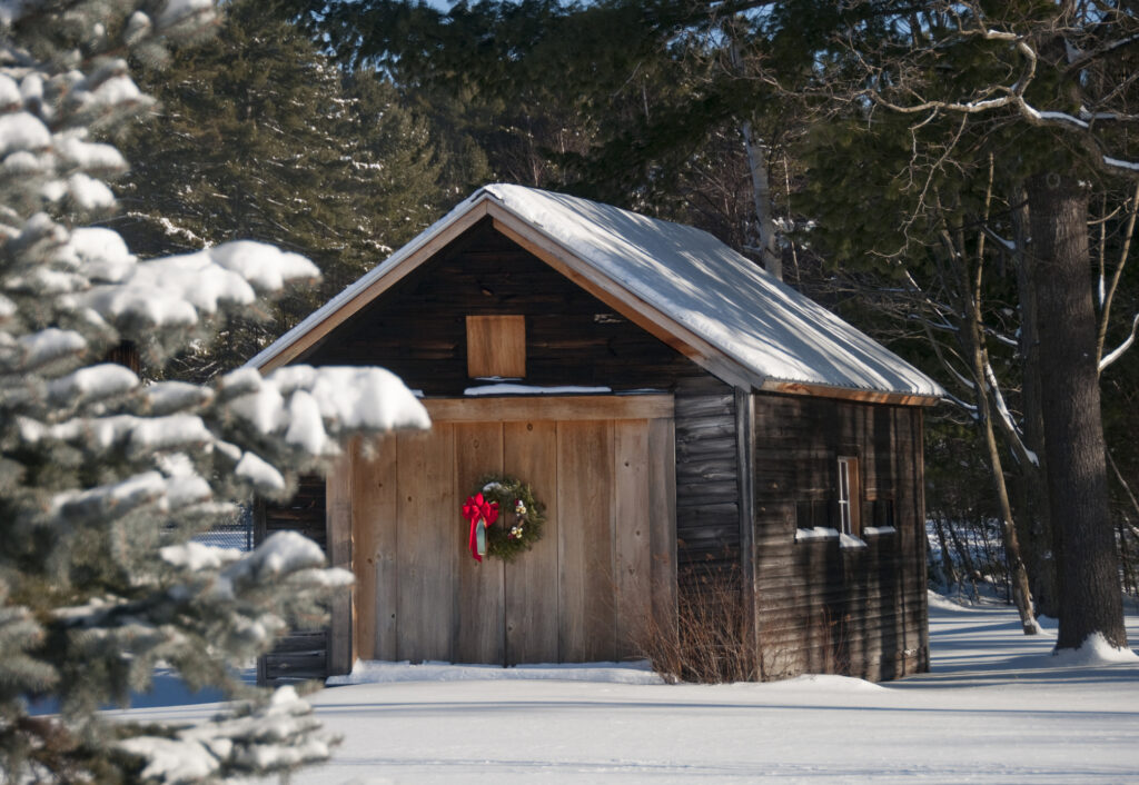 Country barn with holiday wreath in after fresh snowfall.