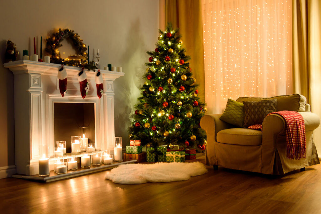 A cozy living room lighted with numerous lights decorated ready to celebrate Christmas. Christmas room interior design, Xmas tree decorated by lights, candles and garland lighting indoors fireplace.