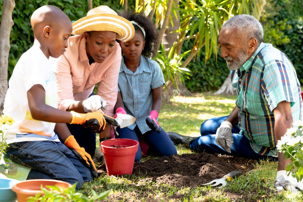 Senior African American couple with their granddaughter and grandson in the garden