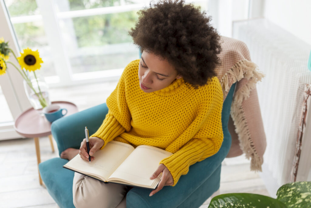 Portrait of a beautiful mixed race woman sitting in an armchair, making a schedule and writing in a planner