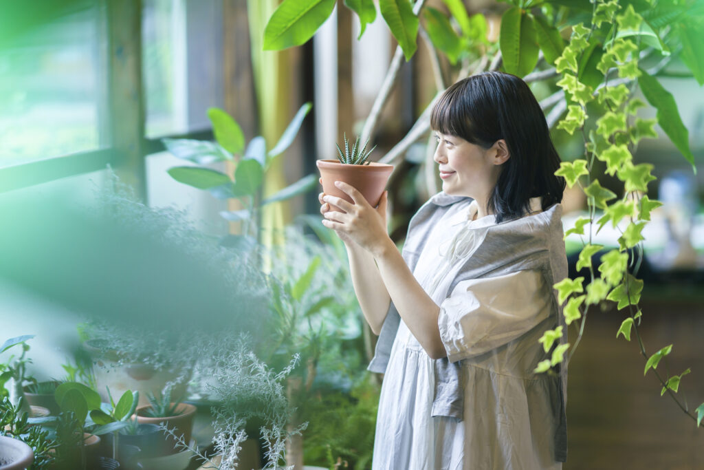 A woman standing next to the window with her houseplants